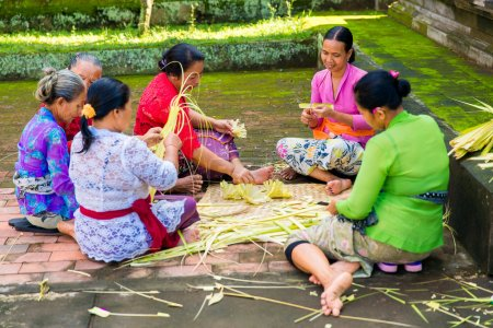 Bali, Indonesia, May 3, 2015. Balinese women make decorations of