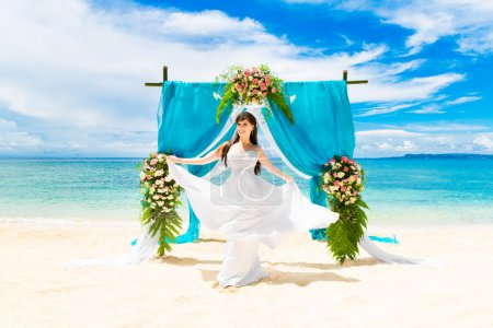 Photo pour Cérémonie sur une plage tropicale. Joyeux mariée sous l'arc de mariage décoré de fleurs sur la plage de sable tropical. Concept de mariage et lune de miel . - image libre de droit