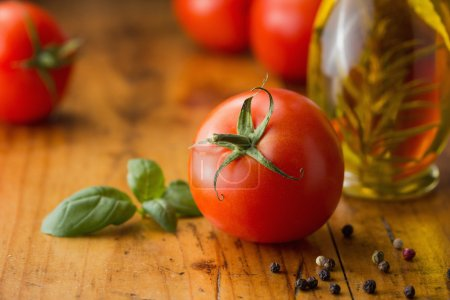 Photo for Tomatoes, basil, olive oil and  peppercorns on a wooden table - Royalty Free Image