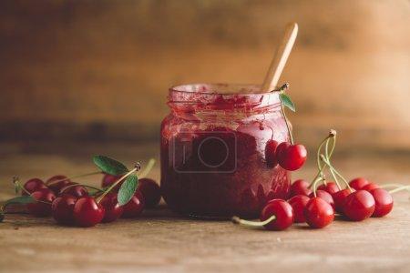 Photo pour Pot de confiture de cerises, cerises acides et cuillère - image libre de droit
