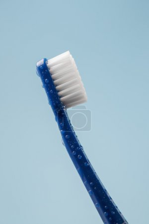 Blue toothbrush with water drops