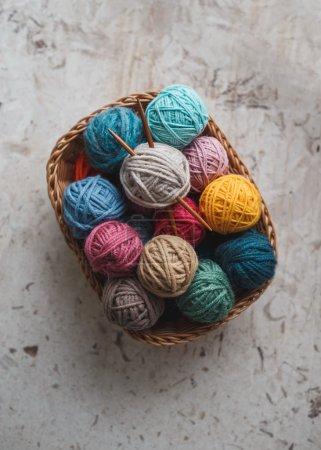 needles and yarn balls in basket