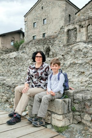 woman and boy sit on ancient blocks