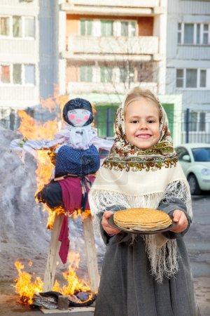 Little girl holding plate of pancakes