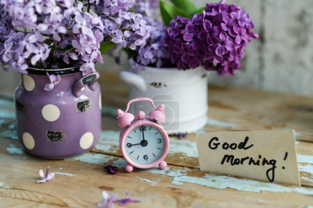Photo for Two tone Lilac flowers in a ceramic pots white and purple, with pink vintage tiny alarm clock and a Good Morning note on a shabby wooden surface - Royalty Free Image