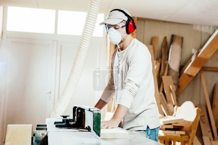 Carpenter working cutting some boards, he is wearing safety glasses and hearing protection