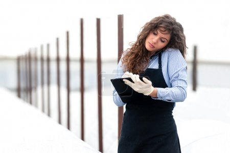 Female researcher technician studying with a clipboard, pen and gloves,