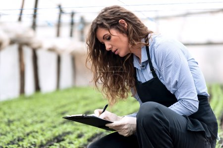 Biotechnology woman engineer with clipboard and pen, examining plants for disease