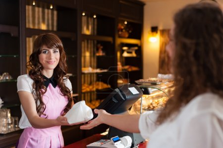 Photo for Happy young smiling seller gives pastry to customer - Royalty Free Image