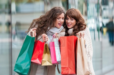 Two beautiful women looking inside shopping bags in the city over shop windows background