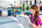 Young woman tourist holding a map in a bus station, looking for direction Madrid, Spain.