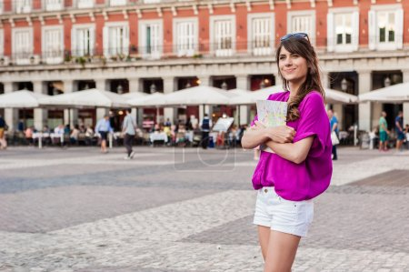 Young woman tourist holding a paper map in Plaza Mayor square, Madrid, Spain, looking for direction.