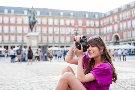 Young woman tourist holding a photo camera and taking picture in Plaza Mayor square, Madrid, Spain