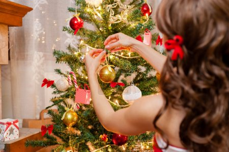 Photo pour Plan rapproché de jolie jeune femme dans la robe rouge et blanche de Noel et le long beau cheveu, décorant l'arbre de Noel au-dessus du salon. - image libre de droit