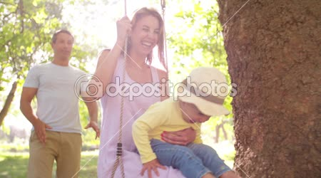 Family with little girl swinging in park