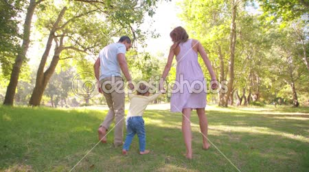Parents swinging a little toddler girl