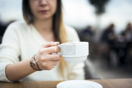 Woman holding a white coffee cup.