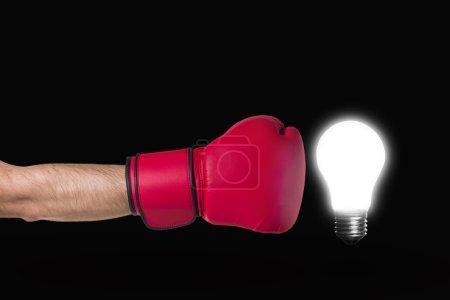 Photo pour Gant de boxe et lampe dans un même cadre sur fond noir . - image libre de droit