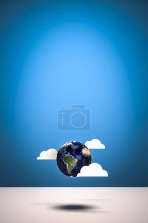 Photo pour Terre avec de faux nuages sur fond bleu studio. Objet conçu en 3D. Illustration . - image libre de droit