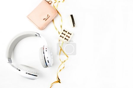 Photo for Music headphones, gold ribbon and blush handbag on white background top view. Mock-up. Feminine scene. header site or hero site. Blog image. Flat lay - Royalty Free Image