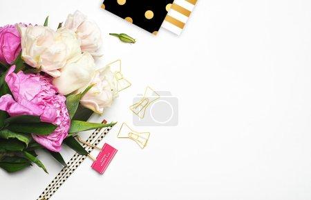 Fond blanc, table de vue, pivoines avec papeterie, agrafes dorées, crayon, motif polka doré et motif rayures dorées