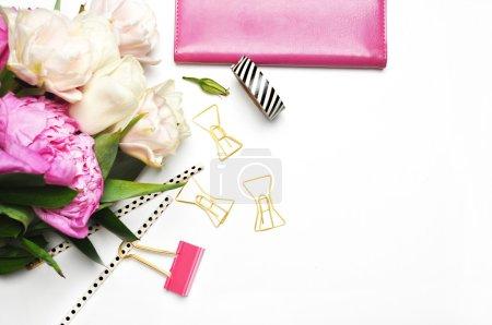 Fleur et articles de papeterie table blanche. Fond maquillé. Scène féminine