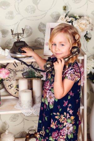 Photo pour Mignonne petite enfant fille avec les fleurs de printemps, heureux bébé fille avec panier de fleurs. Téléphone rétro, un rack avec fleurs et attributs mignons - image libre de droit