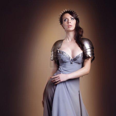 Foto de Retrato de un guerrero de la bella dama, vestido de chica pelo oscuro en un color gris. maquillaje brillante, peinado, picos - Imagen libre de derechos