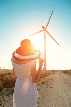 beautiful woman in sunhat and white dress walking near wind turbines at sunset on a hot summer day