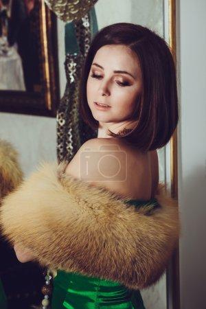 Fashion photo of gorgeous woman with dark hair in elegant green