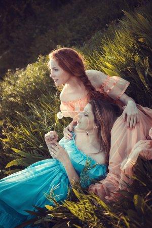 Beautiful women enjoying lilac garden, young women with flowers