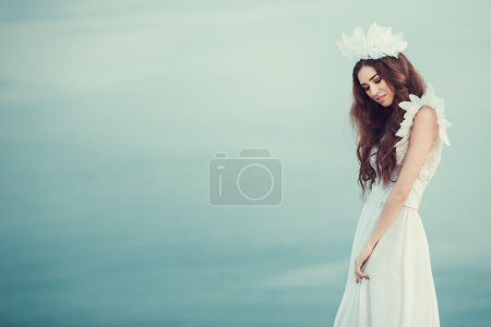 Beautiful bride posing on the coast with angelic dress