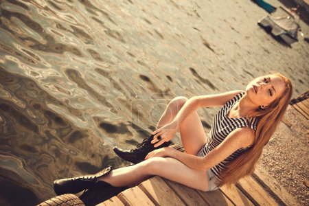 Beautiful sexy woman is dressed in a sea stripped vest sits on the seashore dreams.