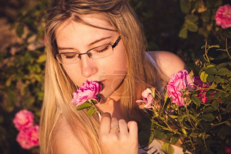 Beautiful woman in garden with roses at sunset