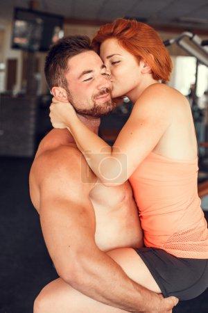 Foto de Pareja en un gimnasio haciendo aeróbic o calentando con gimnasia y ejercicios de estiramiento. amor en los ejercicios - Imagen libre de derechos