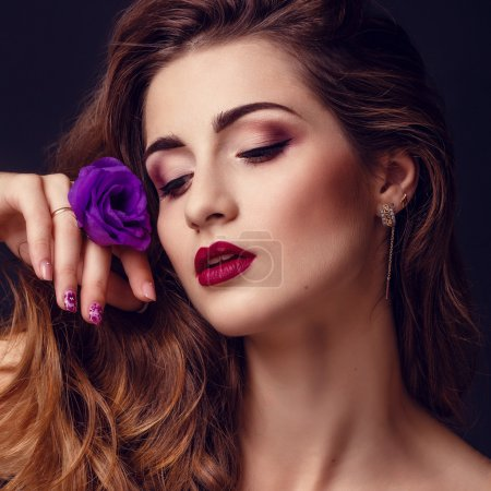 fashion studio photo of beautiful brunette woman with bright makeup with a bouquet of purple and white eustoma