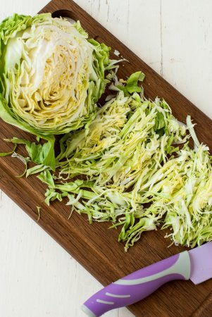 forks young cabbage on a cutting board and knife