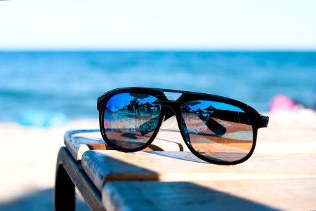sunglasses lie on a beach on sand