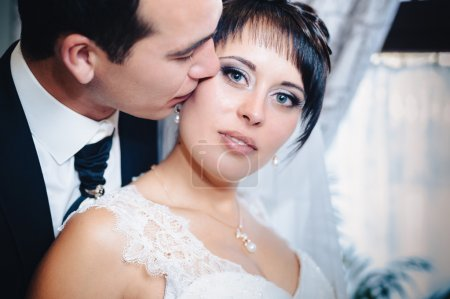 Charming bride with groom embraces and kisses on their wedding celebration in luxurious restaurant. bouquet of flowers, bridal dress. newly married couple atluxury modern hotel hall