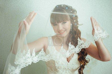 Photo pour Jeune belle mariée attend marié près de la fenêtre. Belle Mariée éclairée par la lumière du soleil depuis une fenêtre. belle jeune mariée debout à côté d'une grande fenêtre d'attente - image libre de droit