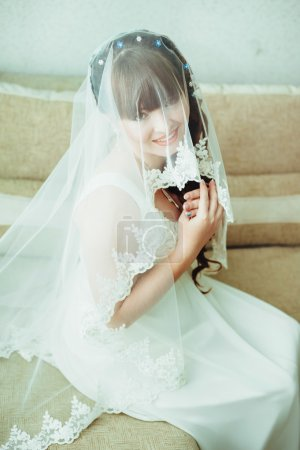 Photo for Young beautiful bride waits for groom near the window. Beautiful Bride lit by sunlight from a window. beautiful young bride standing beside a large window waiting - Royalty Free Image