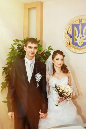 Photo for Wedding ceremony. Registry office. A newly-married couple signs the marriage document. Young couple signing wedding documents - Royalty Free Image