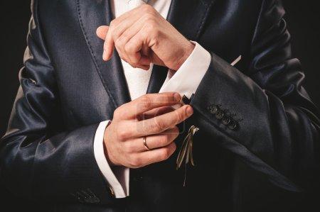 Hands of wedding groom getting ready in suit. black studio background