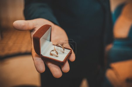 Groom holds a jewelry gift box with gold wedding rings. Man in suit and tie holding engagement ring