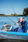 Newly married couple riding in boat on river