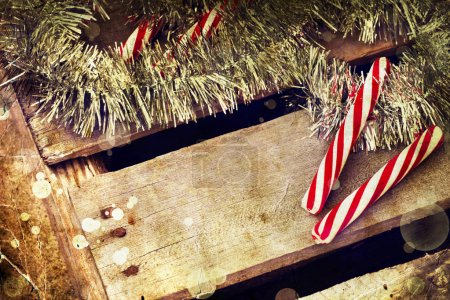Photo for Christmas candy canes wit holiday tinsel on wooden background - Royalty Free Image