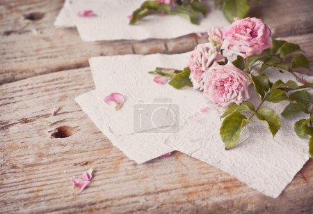 Photo pour Roses roses sur fond de table en bois avec des papiers blancs faits à la main comme espace de copie, thème floral romantique - image libre de droit