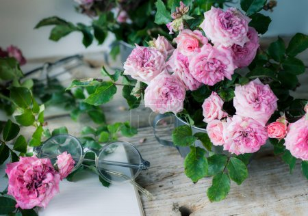Photo pour Roses roses avec verres rétro sur fond de table en bois. Thème floral romantique - image libre de droit