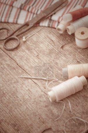 Photo pour Ciseaux, bobines avec filetage, tissu. Ancien kit de couture sur le vieux fond en bois. Fond Vintage - image libre de droit