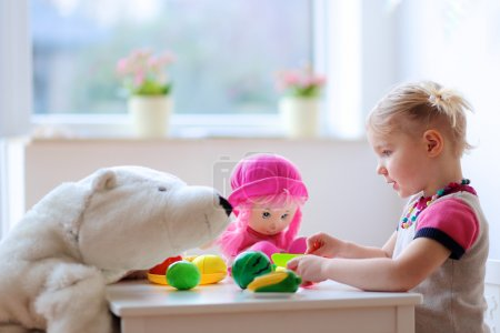 Toddler girl playing with toys indoors